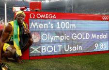 Usain Bolt pózol az időeredményével az Omega berendezése mellett a riói olimpiai 100 méteres síkfutás döntője után